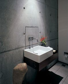 Simple bathroom sink looks contrast with concrete wall
