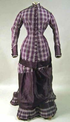 Dress, 1876-78, at the Manchester City Galleries. Purple silk dress with checkered pattern in white and purple satin. Two piece.