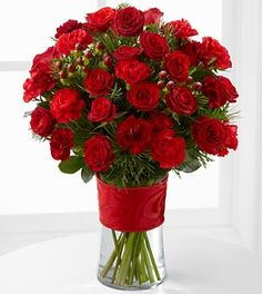 The Spirit of the Season Bouquet bursts with beauty and cheer to dazzle your special recipient with its holiday beauty. Brilliant red spray roses and mini carnations are brought together with burgundy mini carnations, red hypericum berries and assorted holiday greens in a clear glass vase accented with a thick red designer ribbon to create a special sentiment of seasonal wishes and caring kindness.