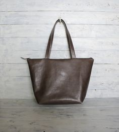 Color is little bit Grege like . This Beautiful Gray Soft leather tote bag is fully lined with thick Gray canvas with 4 large open pockets and one small zipper pocket. Top Zipper closure with leather zipper pull. This Beautiful Leather Tote Bag is Roomy enough for all your daily essentials and would work great all year round. The leather handles are strong enough to carry your laptop, Books and fit comfortably over your shoulder.