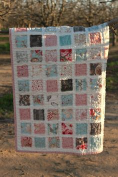 """Baby quilt made from the Vintage Baby Quilt pattern, using Moda's Papillion fabric line.  Blue, pink, grey, red prints. Click photo to see additional pics in my Picasa album. I love this pattern because you're quilting through all layers when you attach the raw-edged squares to the muslin on front. It uses a total of 169 2.5"""" squares. Yes, that's a lot of squares. I cut charm pack squares into quarters, but you could also use jelly roll strips."""