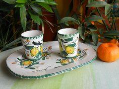 Servizio da limoncello in ceramica,composto da 2 bicchierini su vassoio ovale piccolo,realizzato e dipinto a mano,con materiali e colori atossici;decoro tipicamente siciliano con limoni. Pezzo unico.