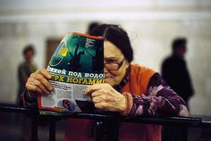 READING - photography by Boogie - Moscow, Russia 2015: I was drawn to this image due to the fact that the woman's face is partial obscured by the newspaper. The photographer has managed to capture a photo of a character that is stereotypically representative of her nationality. The bright colours of the woman's clothes and the newspaper strongly contrast the achromatic colour screen depicted in the background. Bright Colours, Moscow Russia, Woman Face, Newspaper, Contrast, Clothes For Women, Reading, Photography, Character