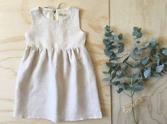Girls babydoll dress made of 100% Linen. Natural light beige colour with a slight two tonal yarn. This gorgeous summer dress features a round neck
