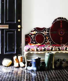 Black door juxtaposed with eclectic settee