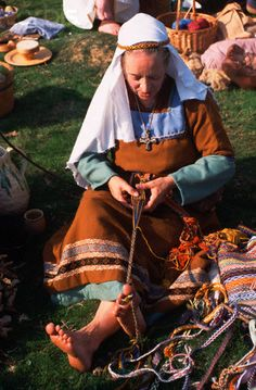 Reenactor tablet weaving, backstrap style with big toe used to tension the warp