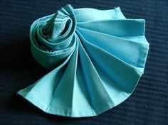 Dramatic fan napkin folding. Almost looks like a nautilus shell.