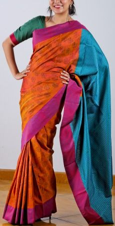 This flame orange Kanchipuram saree has a navy blue floral printed body. This is further enlivened with a magenta striped border and a block printed pallu in turquoise blue.A saree for the happy occasions in life, certainly! SHOP AT www.ubikaa.com