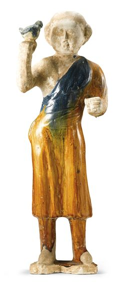 A RARE BLUE AND OCHRE-GLAZED POTTERY FALCONER<br>Tang Dynasty | Lot | Sotheby's