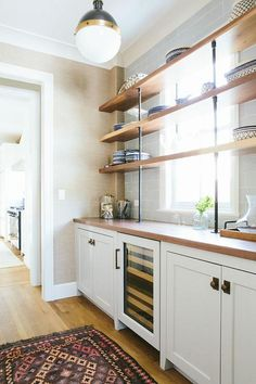 Chic butler's pantry features a Hicks Pendant illuminating white shaker cabinets adorned with aged brass vintage hardware fitted with a glass door wine cooler topped with wood placed under wood and pipe shelves lining a gray subway tiled wall and placed in front of a single window.