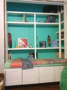Add a bench with hidden storage cabinets to the interior of a closet. Include pillows to create a welcoming cozy place to sit and relax. Add white shelving to colorful walls to finish off this cozy sitting area.