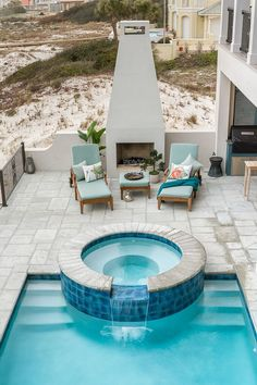 Inviting outdoor space with fireplace, hot tub, and pool