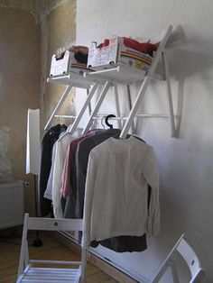 Store folding chairs on the wall  as clothes racks and shelves.