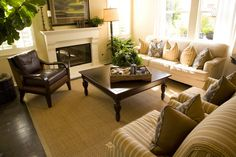 A familiar large dark wooden coffee table separates tan couch and armchairs from traditional wood and leather reading chair in this sunny room.