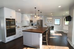 remodeled kitchen with farm sink island, inset appliances, professional stove and hood, wine frige, and built in bench seating