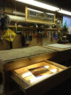 "~The ""Glass Dungeon"" ~ Stained glass workbench with pegboard tool storage and light table built into a drawer. Large PVC tubes work great for storing lead came and pieces of zinc."
