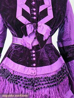 HIGH STYLE PURPLE RECEPTION GOWN, 1870s Jacket & bustle skirt of vibrant purple silk faille & darker purple velvet, peplum jacket w/ silk & chenille ball fringe, long side panels, 1 side panel w/ gathered & bow decorated pocket, decorative bows throughout, ivory silk jacket lining, brownpolished cotton w/ bustle tape skirt lining, original belt. Detail