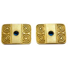Antique Russian Sapphire Gold Cufflinks. Archaeological Revival Antique Russian Cufflinks  Made in Moscow between 1908 and 1917  Of rectangular shape with rounded corners, each centered with a cabochon-cut blue sapphire on a plain matte ground bordered with two pairs of ancient style scrolled decorations