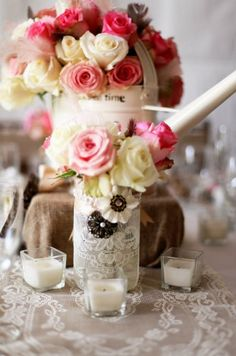 Rustic wedding centerpieces with roses and watering cans.