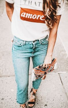Casual outfit for spring or summer. Distressed jeans, T and cute clutch
