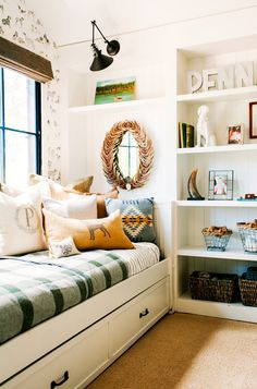 Built-in bookshelf in little boys room with daybed and lots of pillows
