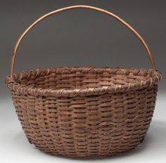 """SHENANDOAH VALLEY OF VIRGINIA WOVEN SPLINT EGG BASKET, white oak, finely woven circular form with X-wrap rim, high arched handle and kick-up bottom. Original dry natural surface with outstanding patina. Probably by a member of the Nichols family of basketmakers, Page Co., VA. Late 19th/early 20th century. 8 1/2"""" HOA, 9 1/2"""" D."""