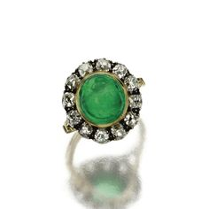 CABOCHON EMERALD AND DIAMOND RING, LATE 19TH CENTURY. The oval cabochon emerald measuring approximately 10.4 by 9.9 by 7.9 mm., encircled by 12 old-mine diamonds weighing approximately 1.45 carats, mounted in gold and silver