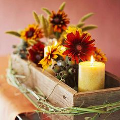 A rustic rectangular container disguises a few small flower vases, making a great way to create an eclectic collection of blooms, fall foliage, and candles. Tie long grass or fall berries around the container to make the decoration pop.