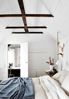 Minimal, effortless bedroom with white shiplap walls, exposed wooden beams, neutral bedding and light fixture suspended by rope | Lynda Gardener