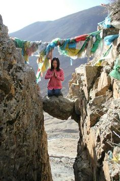 A young girl is praying on the rock between two hills, Lhasa, Tibet