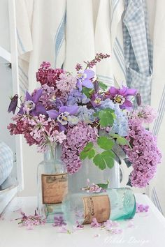 Spring lilacs and pansies in old vintage sea blue bottles with blue and white checkeredapron and grain sack - perfect country farmhouse style!