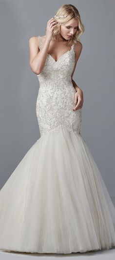 This gorgeous mermaid wedding dress features a bodice of beaded lace appliqués accented in Swarovski crystals atop a tulle skirt. Embellished spaghetti straps glide from the sweetheart neckline to illusion V-back accented in beaded lace appliqués. Finished with covered buttons over zipper closure.