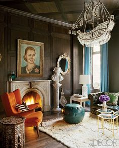 great dark brown stain wood paneled walls and ceiling ~ crystal ship chandelier ~ teal and orange color scheme ~ great classic, formal living room ~ and is that Ava Peron on the wall?