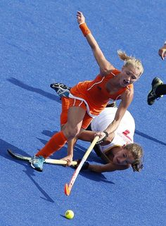 Netherlands' Maartje Goderie (front) jumps over Belgium's Judith Vandermeiren's stick as they fight for the ball during their women's Group A hockey match at the London 2012 Olympic Games at the Riverbank Arena