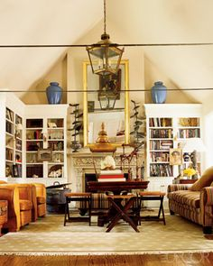 bookshelves, campaign stools, gilded mirror, lantern fixture, vintage leather armchairs, and vaulted ceiling.  elle decor.