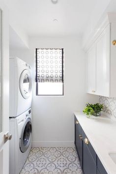 Small blue and white laundry room features a stacked washer and dryer placed on Granada Normandy Tiles facing white upper cabinets mounted above dark blue shaker lower cabinets finished with brass cup pulls and a white quartz countertop fixed against Granada Normandy backsplash tiles.