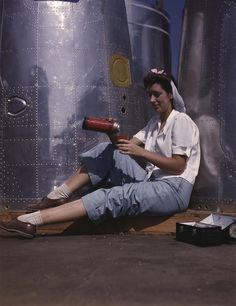 Woman working on an airplane motor at North American Aviation Inc, plant in California, 1942. (Photo by Alfred T. Palmer/Buyenlarge/Getty Images)        This girl in a glass house is putting finishing touches on the bombardier nose section of a B-17F Flying Fortress navy bomber, Long Beach, Californ