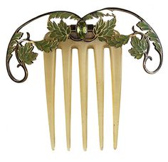 """This art nouveau comb sold for 3086.61$ at the Hôtel des Ventes Genève. Hinged to horn, a tiara of green foliage is held together by blue enamel branches. The leaves are made of plique-à-jour enamel encased in gold. In the center resides a marquise-shaped peridot. The stamp on the back reads """"JserpentB,"""" and it comes in its original case. c. 1900."""