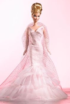 Designer Robert Best creates Pink Ribbon™ Barbie® doll, a wonderful tribute to the Susan G. Komen Breast Cancer Foundation. Joining the fight against breast cancer, Barbie® doll wears a frothy pink organza gown featuring a shirred design with tiers of ruffles. An attached, pink ribbon proudly states Barbie® doll's support. A sparkly, tulle stole and long pink gloves complete the stylish ensemble!