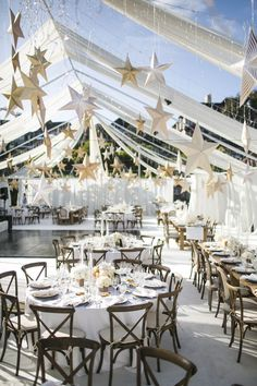 The groom's family's backyard tennis courts were transformed into an elegant reception space with creamy drapery and rustic, wooden tables. Rows of cascading icicle lights and gold paper stars were suspended overhead from invisible threads. #reception #decor #tent Photography: Samuel Lippke Studios