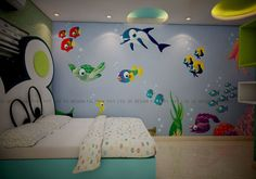 The kid's bedroom looks virtually like a wonder world with its bright green and blue finish and wall paintings. The colourful and comical fishes swimming in azure blue waters create a stunning effect that it joyful.  The blue and green wardrobe has flowery handles and the study unit is also inviting. Overall it is a cosy and colourful life for the kid.