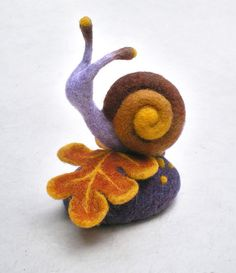 A curious snail quietly goes his way on a fall leaf... This peaceful needle felted nature miniature is a nice decoration for your home or your office, but also can be an original pincushion into which you will stick your pins and needles.  A wonderful gift for someone who likes needlecraft!  The interior of the base is from high density foam which is covered with felted wool. This gives stability to the miniature. The snail and the leaf are from felted wool only. I use a combination of…
