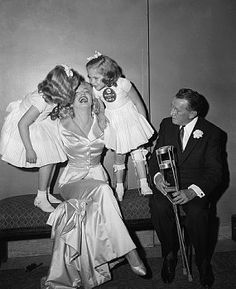 January 28 1958 :Actress Marilyn Monroe Miller is kissed by the march of dimes poster twins, six-year-old Lindy and Sandy Sue Solomon at today's annual March of Dimes fashion show in the Waldrof-Astoria. Miss Monroe wore a long champagne toned silk satin dinner costume of a form fitted jacket designed by John Moore for Talmack. The show featured fashions by members of the couture group of the New York Gress institute and other designers of New York, California and Italy