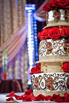 That is an Amazing red white & gold wedding cake! So royal looking