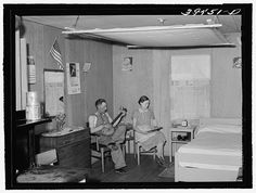 Farm worker and his wife in their cottage at the FSA (Farm Security Administration) labor camp. Caldwell, Idaho. Notice the quilt on frame near the ceiling