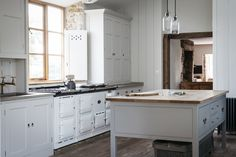 Dorset Farmhouse Kitchen by Plain English featuring handcrafted Counter standing Cupboards, marble worktops and an island with a Pippy Oak wooden worktop. Worktable. Honed Oyster Stone.