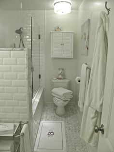 Beautiful mix of beveled white subway tile and carrera marble.  I really like the tile work and maybe we could combine our shower and tub to have space for a toilet room?