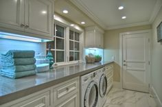 what casts the blue light - lovely laundry room with great long counter & lovely floor - gorgeous, yet understated