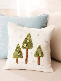 knitted christmas trees on a pillow