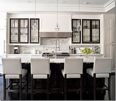 Nice and simple white kitchen with pretty clear glass mini pendants over the island. I like the white barstools. Dark trim on upper cabinets is a different way to add pizzazz. Link has 100 kitchen island ideas and some pretty kitchen designs.